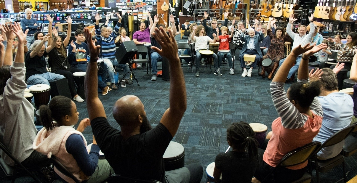 Photo of a group of thirty smiling people sitting in a circle facing each other with their hands up. They each have drums: the tall drums by their feet and small drums on their laps.