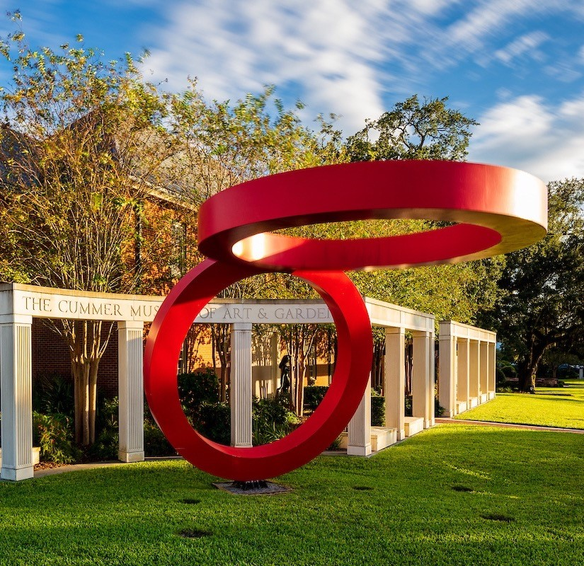 Photo of the outdoor stone columns and the sculpture of two giant, metal, bright red rings. One ring is standing upright and the other ring connects to the top curve, hovering parallel above the ground.