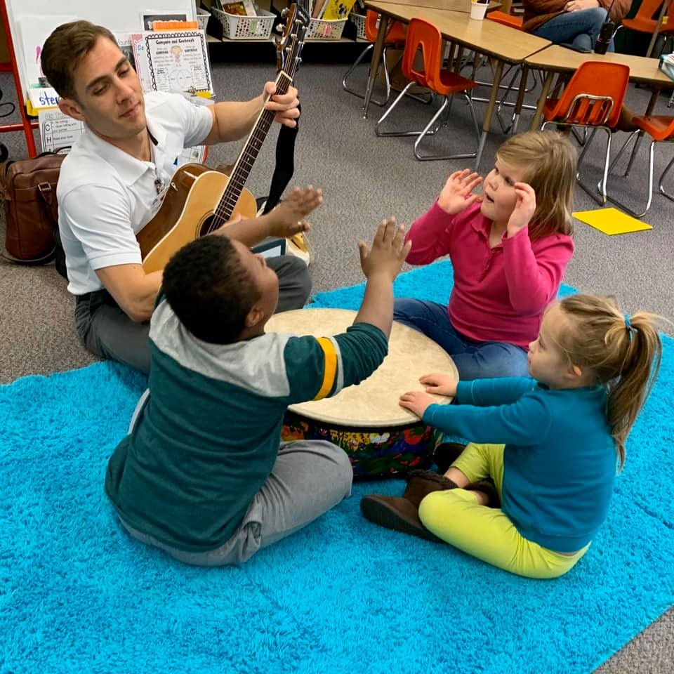 Photo of a music therapist playing the guitar sitting in a small circle with three children playing a large drum together in the center.
