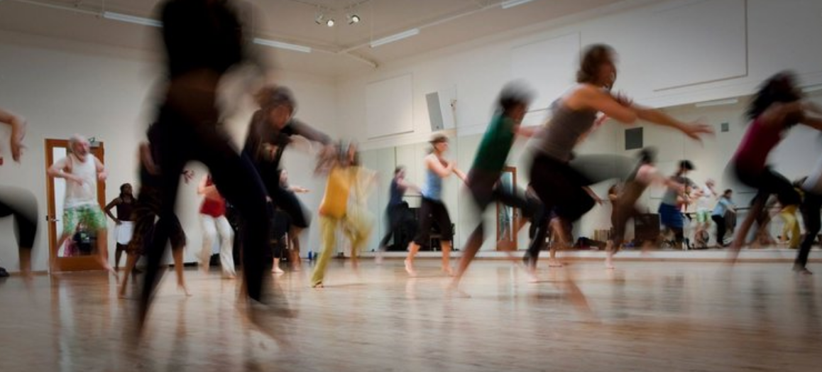 Photo of adults and children stretching, moving, and dancing with creative poses.