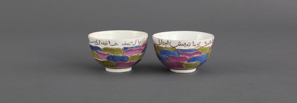 Photo of two small, white tea bowls. There is gold Islamic script along the outer rim with green, blue, and purple layered dabs of organic bean-like shapes around the body of the bowls.